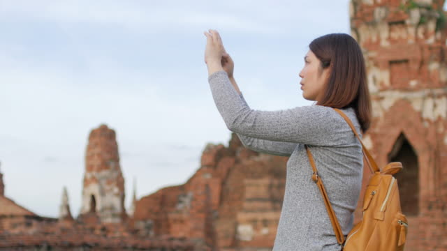 woman traveller using mobile phone for take a photos at ayutthaya historical park thailand - ayuthaya province stock videos and b-roll footage