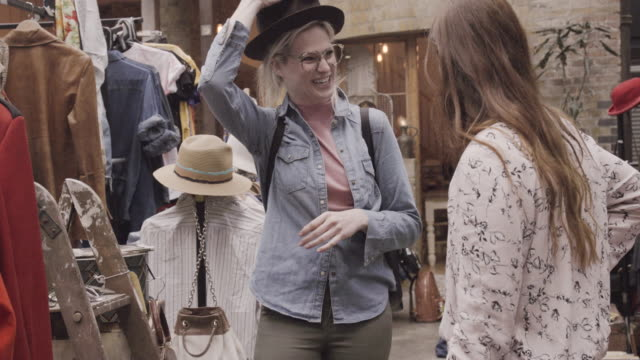 Woman tries hat with glasses in vintage shop, while friend watches and laughs.