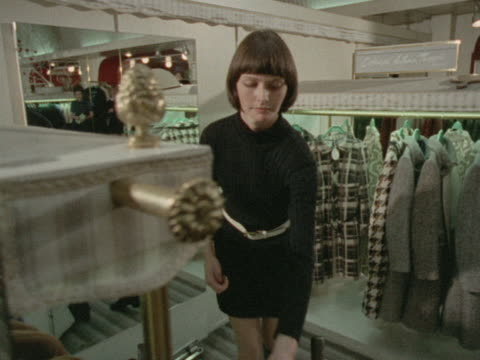 stockvideo's en b-roll-footage met a woman tries on a fringed maxicoat in a clothes shop - kleding