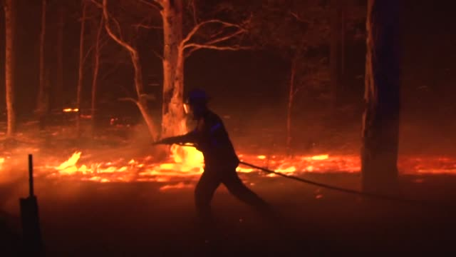 a woman tries to protect her house as blazes burn around nowra in new south wales australia - fire natural phenomenon video stock e b–roll