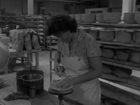 woman trims a shallow bowl at the stavanger pottery workshop. 1959. - stavanger stock videos & royalty-free footage