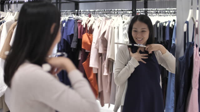 woman try wearing clothes front of mirror in clothing store - boutique stock videos & royalty-free footage