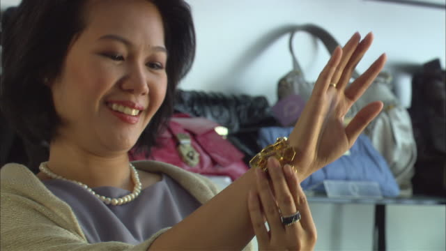 cu, woman trying bangle in jewelry store, singapore - bangle stock videos & royalty-free footage