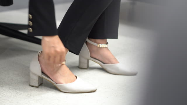 vídeos de stock e filmes b-roll de woman trying black high heels in boutique - cabine de loja