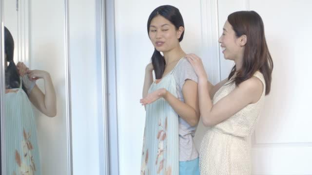 stockvideo's en b-roll-footage met woman trying clothes - haar naar achteren