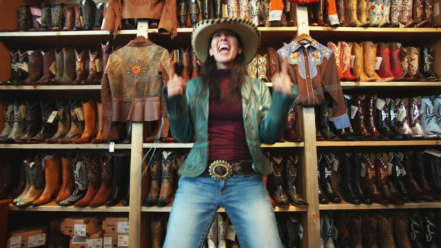 woman trying on a leather jacket and a cowboy hat at a western store