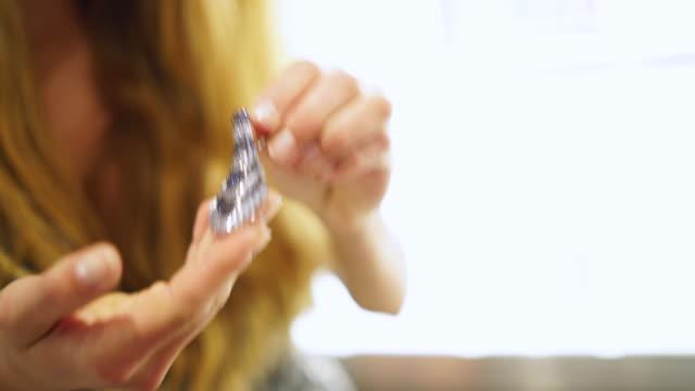 frau, die versucht, auf einen reich verzierten ohrring bei einem juwelier - schwenk nach oben stock-videos und b-roll-filmmaterial