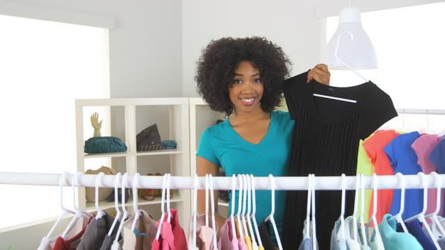 vídeos de stock e filmes b-roll de woman trying on clothes in store - só uma mulher de idade mediana