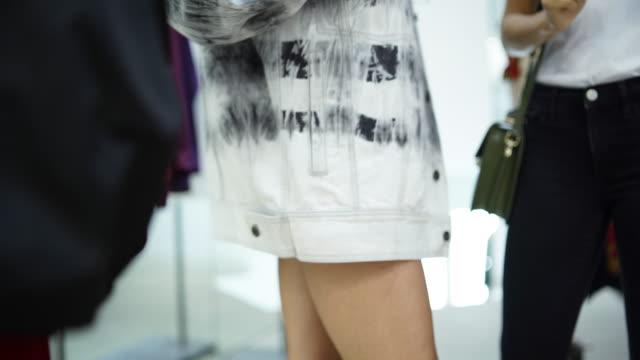 Frau versucht auf Kleidung in einem Geschäft mit Hilfe von einem Freund