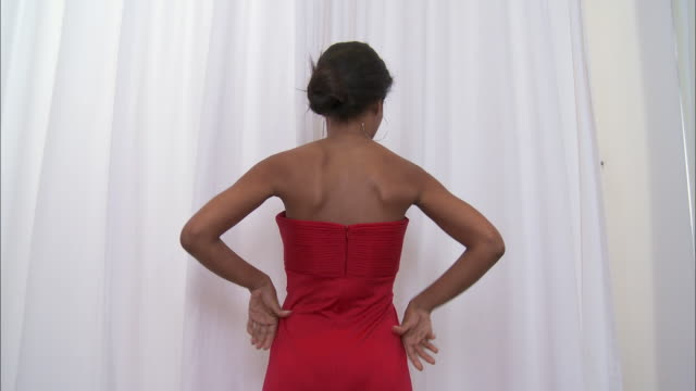 MS Woman trying on elegant red dress in fitting room / Brussels, Belgium