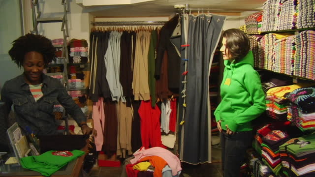 vídeos de stock e filmes b-roll de ms, woman trying on green hooded shirt in clothing store, london, england - escolha