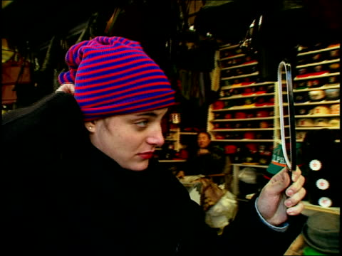 stockvideo's en b-roll-footage met woman trying on grunge hat in nyc store - muts