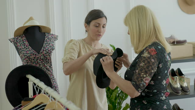 vídeos de stock e filmes b-roll de woman trying on hat in fashion store with saleswoman next to her - viciado em compras