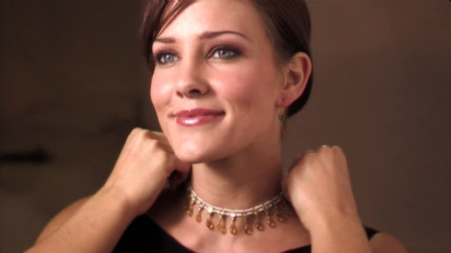 woman trying on necklace - halskette stock-videos und b-roll-filmmaterial