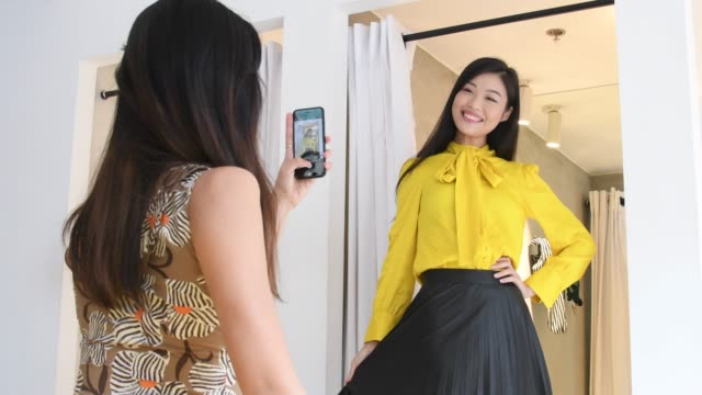 woman trying on new outfit and friend photographing on phone - photographing stock videos & royalty-free footage