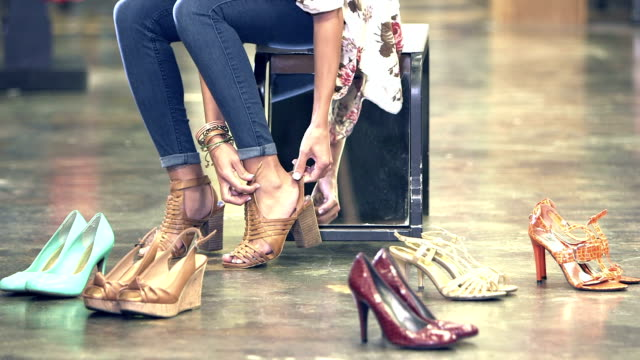vídeos de stock e filmes b-roll de woman trying on shoes in store - fazer compras