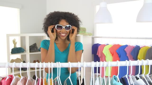 vídeos de stock e filmes b-roll de woman trying on sunglasses in store - só uma mulher de idade mediana