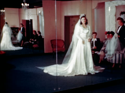 1945 woman trying on wedding dress in shop / industrial