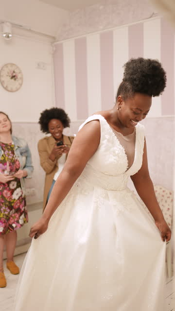 woman trying on wedding dress with female friends having fun and taking photographs. - 20 29 years stock videos & royalty-free footage