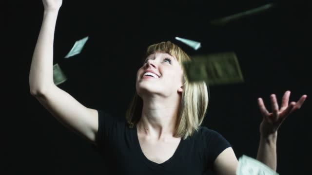 woman trying to catch money as it falls from above