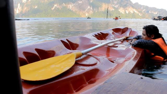 donna cercando di salita canoa - giacca di salvataggio video stock e b–roll