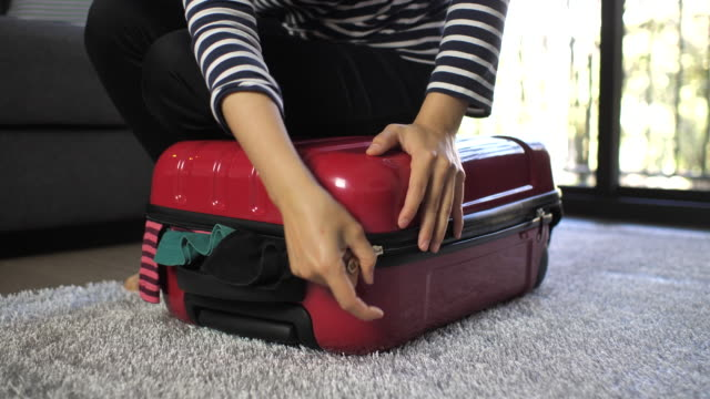 woman trying to close her full suitcase at hotel, slow motion - full stock videos & royalty-free footage