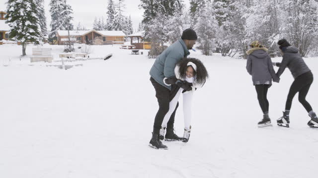 vídeos de stock, filmes e b-roll de woman trying to ice skate on frozen lake nearly falls and is caught by her boyfriend. - 25 30 anos