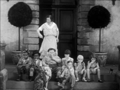 vídeos y material grabado en eventos de stock de b/w 1931 woman trying to shoo our gang children sitting + eating ice cream cones on steps / feature - helado de vainilla