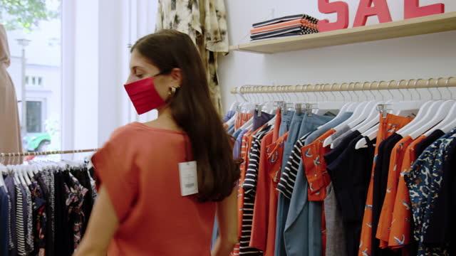 donna che cerca di top nel negozio di abbigliamento durante covid-19 - negozio di abbigliamento video stock e b–roll