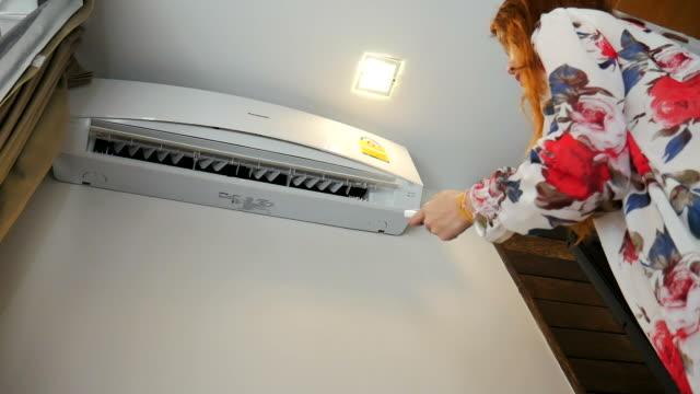 Frau schalten Sie Klimaanlage