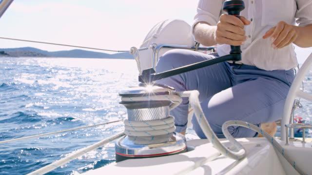 ms la woman drehen eine seilwinde auf einem segelboot - flaschenzug stock-videos und b-roll-filmmaterial