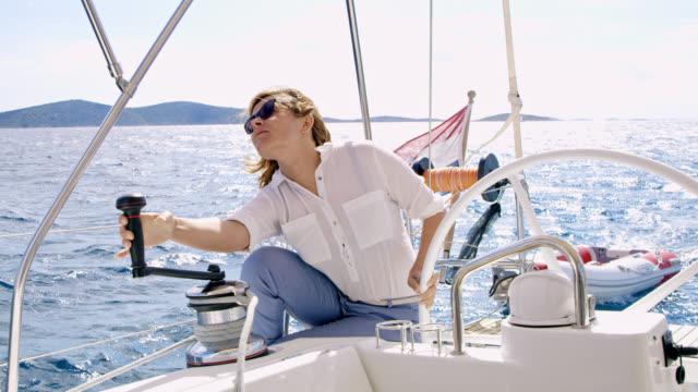 ws-frau drehen eine winde während der navigation ein segelboot - segeln stock-videos und b-roll-filmmaterial