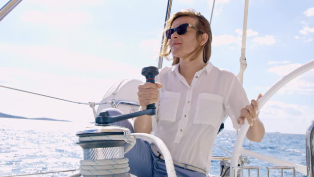 ws la woman turning a winch while navigating a sailboat - crew stock videos & royalty-free footage