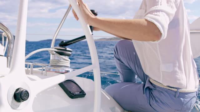 vidéos et rushes de ms la femme tournant un treuil en naviguant d'un voilier - capitaine de bateau