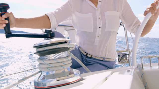 MS Woman turning a winch while navigating a sailboat