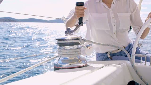ms la woman turning a winch while navigating a sailboat - sail stock videos and b-roll footage
