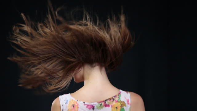 vidéos et rushes de ms slo mo woman  turning around, looking towards, and turning back with hair blowing in wind / london, greater london, united kingdom  - cheveux