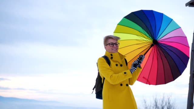 Woman turning around with colorful umbrella