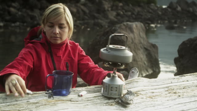 ms woman turning off boiling kettle on camping stove and pouring water into cup, garibaldi provincial park, squamish, british columbia, canada - camping stove stock videos and b-roll footage