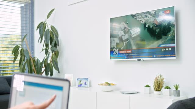 DS-Frau drehen Sie ihr Fernsehgerät mit einer smart home-app auf ihrem tablet