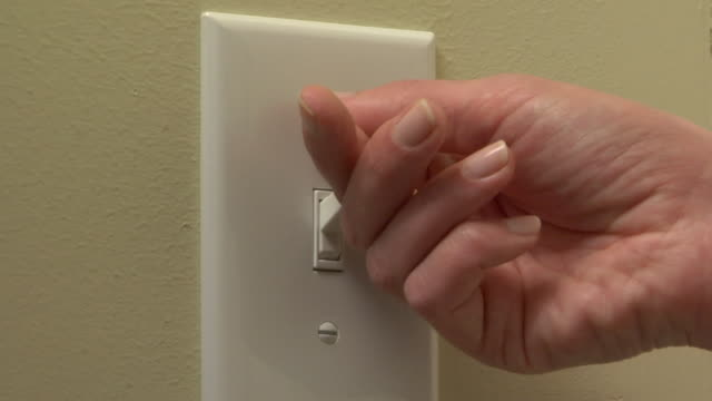CU, Woman turning off light switch on wall, close-up of hand