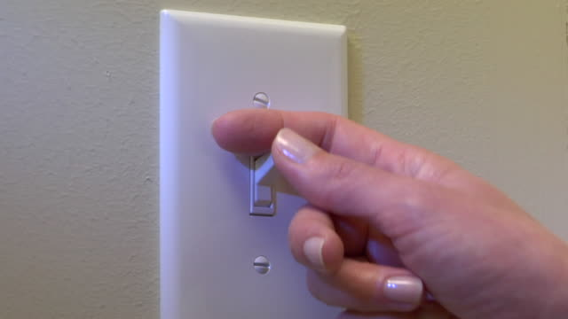 vídeos de stock, filmes e b-roll de cu, woman turning off light switch on wall, close-up of hand - interruptor de luz