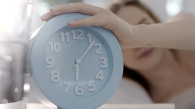 woman turning off the clock alarm and getting up from bed - alarm clock stock videos & royalty-free footage