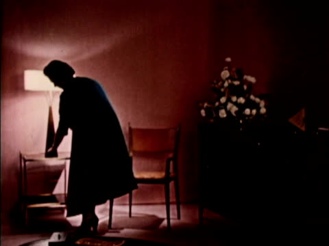 vídeos de stock e filmes b-roll de 1956 ws woman turning on light in darkened living room and taking off coat / usa - menos de 10 segundos