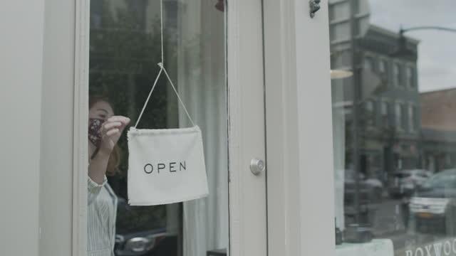vídeos y material grabado en eventos de stock de woman turning sign in shop window - boutique