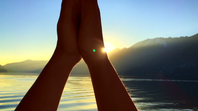 vidéos et rushes de woman turns her hands around the sun and greeting over alpine lake with mountain in sunset - seulement des femmes d'âge mûr