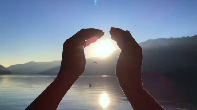 vídeos de stock, filmes e b-roll de woman turns her hands around the sun over alpine lake with mountain in sunset - ilusão
