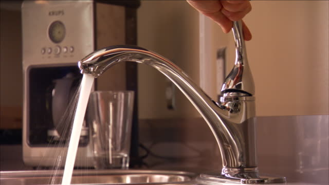 vidéos et rushes de a woman turns the water on and off at her kitchen sink. - lavabo et évier