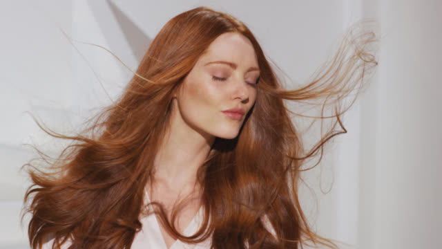 vidéos et rushes de woman turns to camera while red hair blows in breeze - cheveux