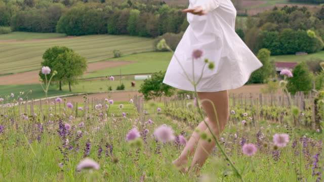 SLO MO Woman twirling among spring flowers on the top of a hill